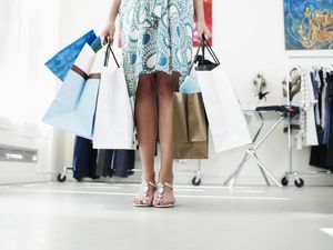 Young woman holding shoppings bags in boutique