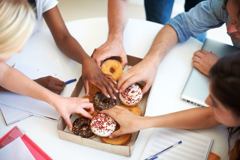 People eating donuts from above.