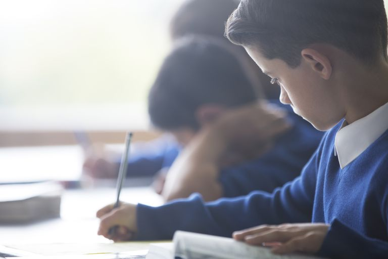 Schoolboys writing at desk in classroom