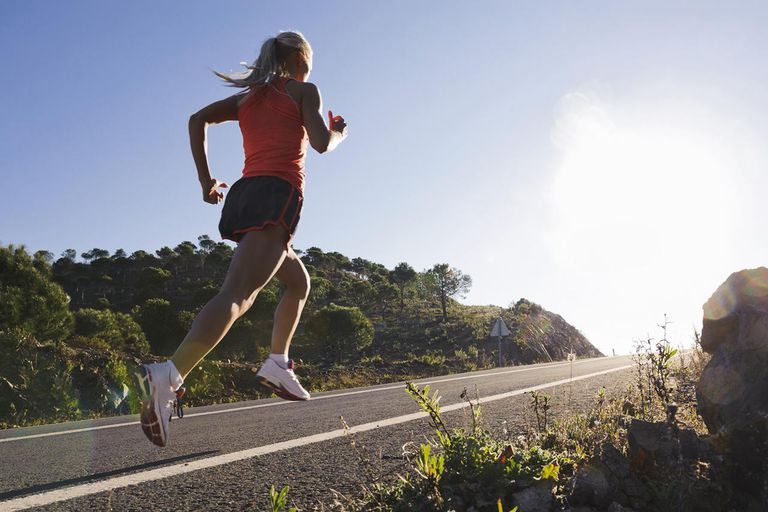 Runner running on road, low angle view
