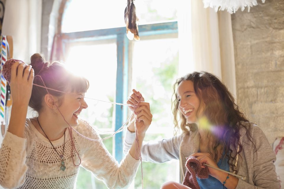 two woman playing with yarn