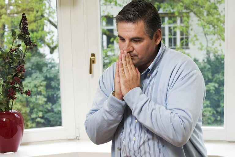 A man praying by a closed window
