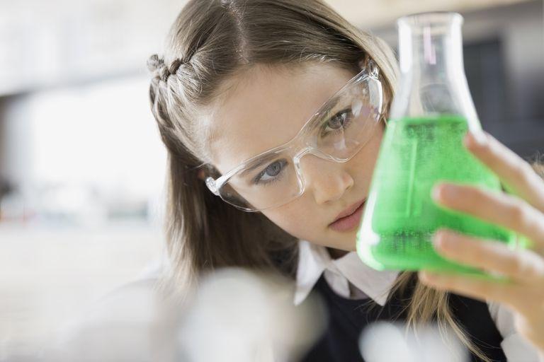 School girl examining liquid in beaker