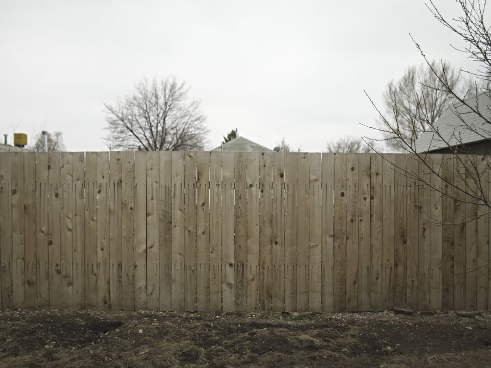 Wooden fencing in an non-landscaped yard.