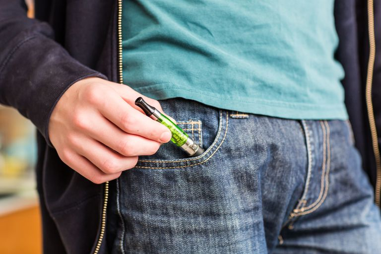 teen pulling vaper out of pocket