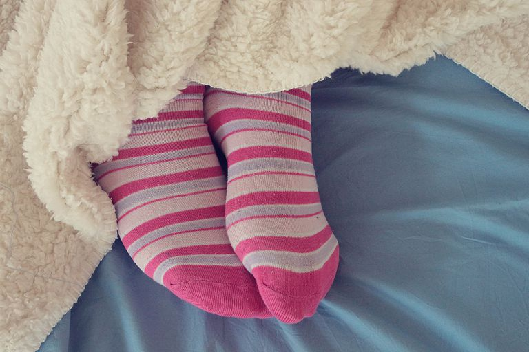 Woman's feet in pink socks sticking out from under a blanket