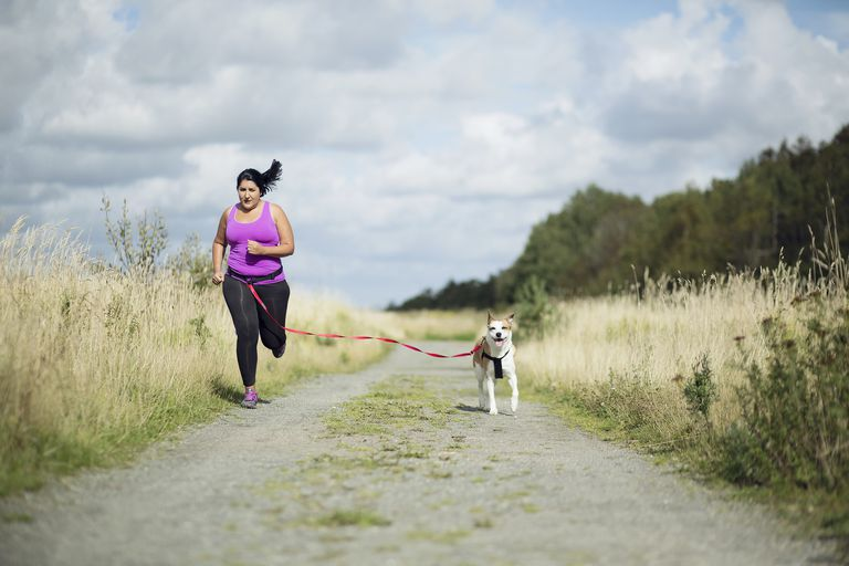 Woman running down a path with her dog
