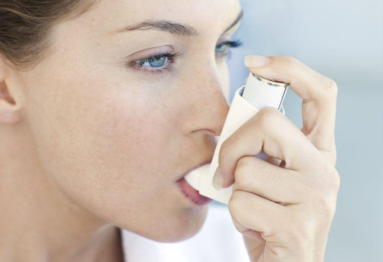Woman using an inhaler.