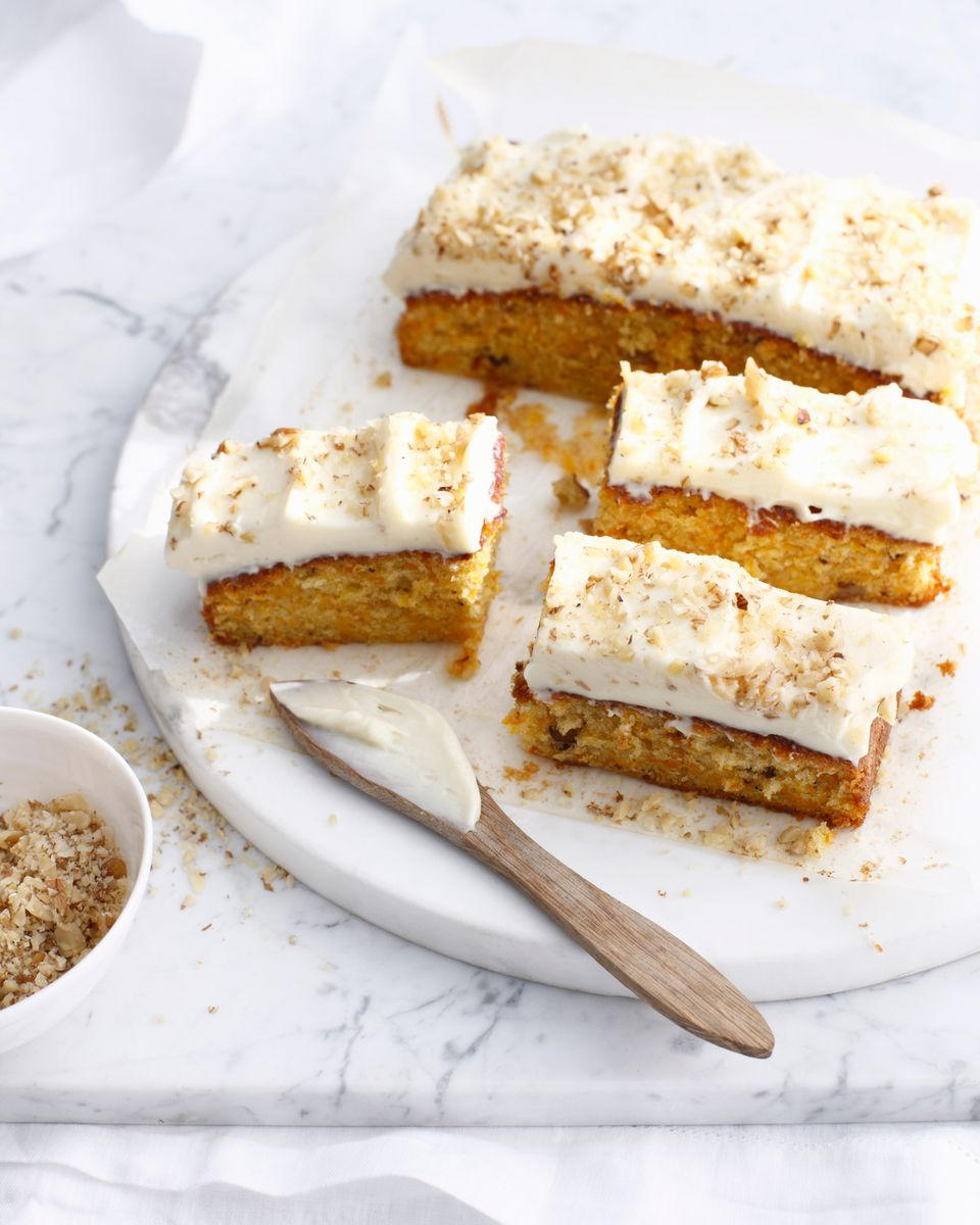 Carrot cake with cream frosting sprinkled with walnuts