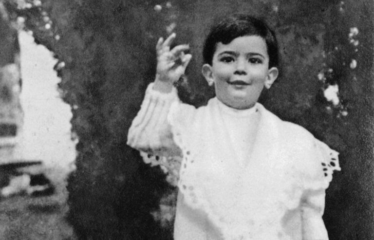 Black and white photo of Salvador Dalí as a child in a ruffled shirt