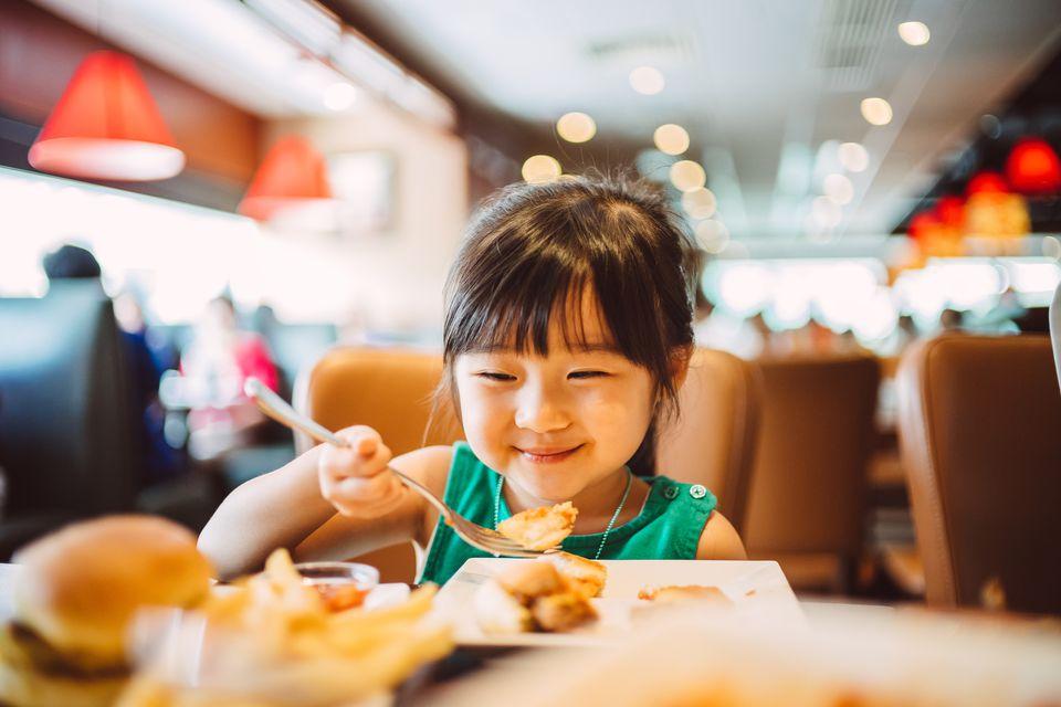 Lovely little girl having meals joyfully