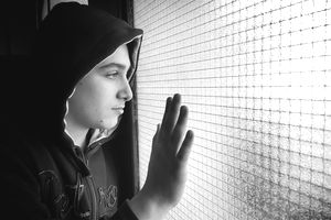 Close-up Of Boy Looking Out Window