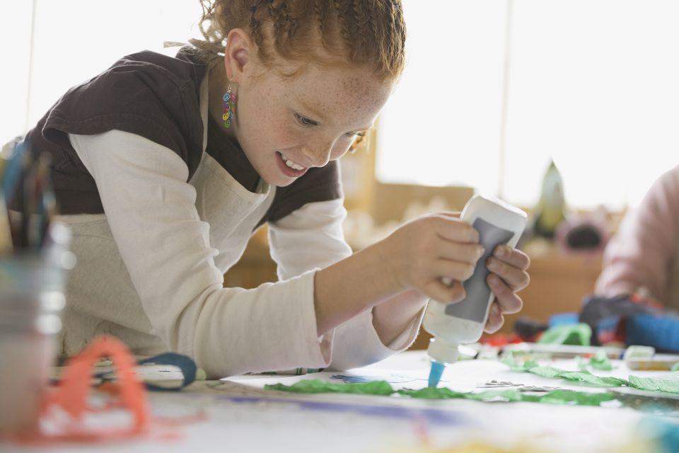 Girl using glue in art class