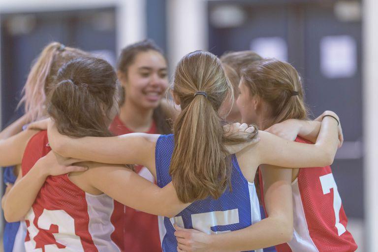 Group of high school female basketball opponents huddled