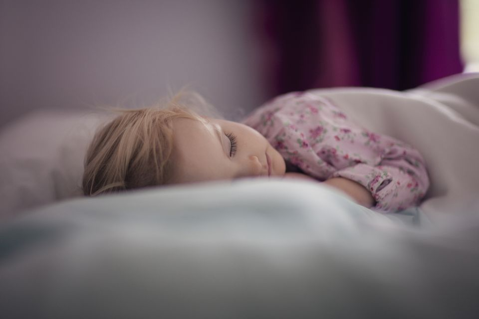 Toddler girl (2-3) sleeping on bed
