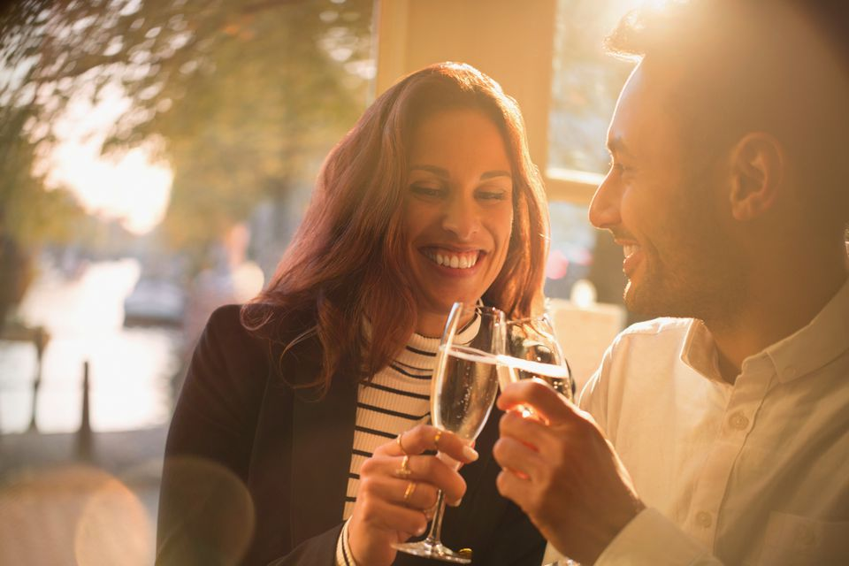 Smiling, romantic couple toasting champagne glasses in restaurant