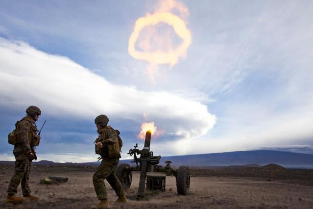 Cpl. Michael Oberley, 1/12 section chief and native of Greeley, Colo., and Cpl. Kyle Beagle, 1st Bn., 12th Marines mortar gunner and native of Deland, Fla., fire a round from 120-mm mortar system during a training session for Operation Spartan Fury, Dec. 2. Marines updated their proficiency in mortar and howitzer shooting drills and applying those skills and techniques to a mock battle scenario.