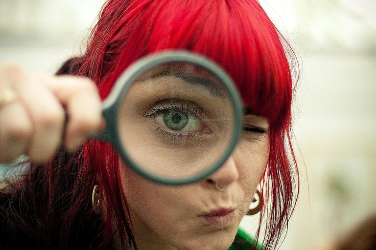 A woman looking through a magnifying glass represents interpretive sociology, which focuses on studying people's lives from their own perspective.