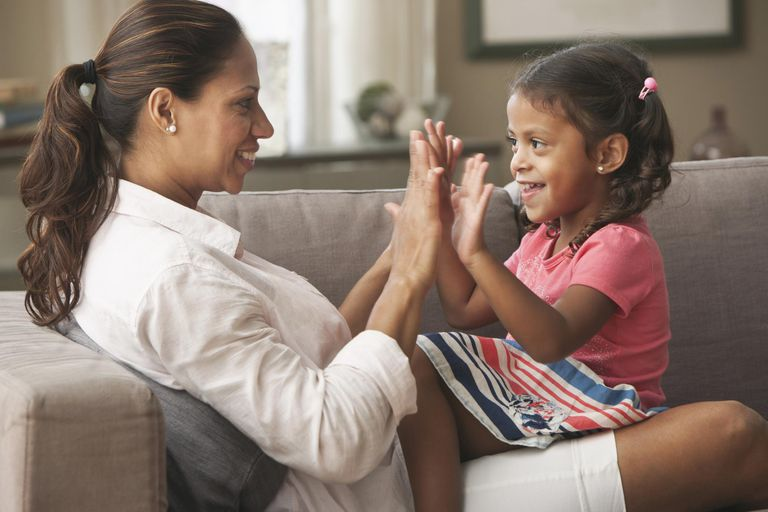 Hispanic mother playing clapping game with daughter