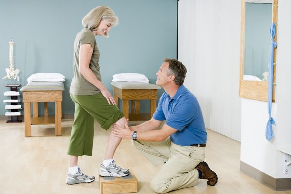 Photo of a physical therapist working with a woman's knee.