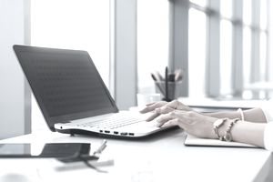 Female worker using laptop in office, working with new project. Woman blogging at home as a freelancer.
