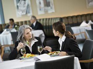 Mature and mid adult business women talking during lunch