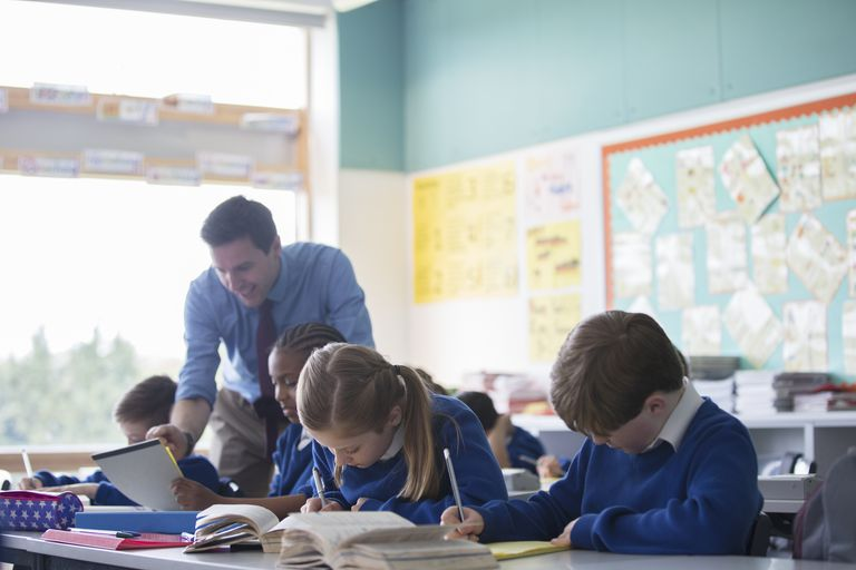 Male teacher assisting elementary school children in classroom during lesson