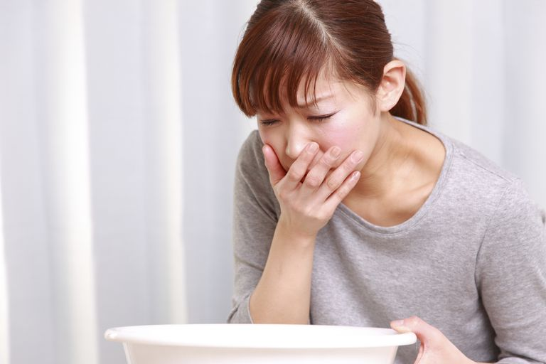 woman next to bowl vomiting