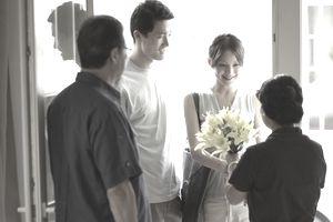 Parents greeting adult offspring at front door