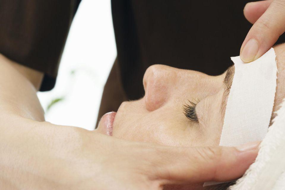 Woman having eye brows waxed, close-up