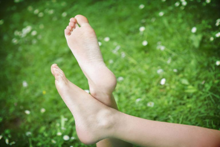Portrait of Young Woman's Feet Relaxing in Field