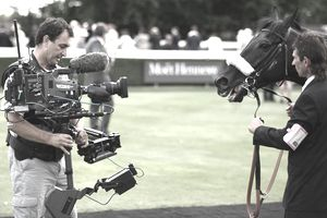 A racehorse being filmed by a TV crew