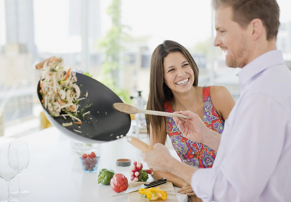 Woman watching husband flipping stirfry in the kitchen