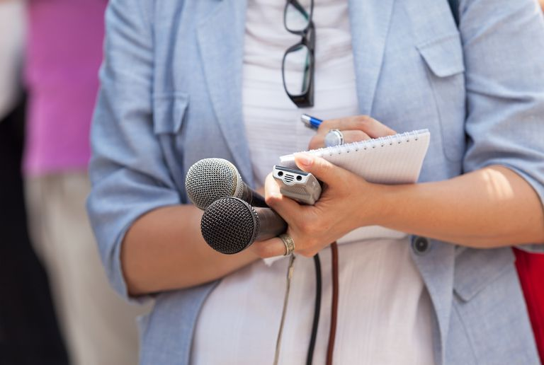 Midsection Of Journalist Writing In Notepad While Holding Microphones