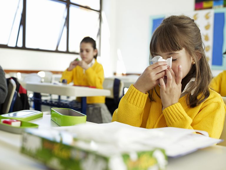 Girl blowing nose in class