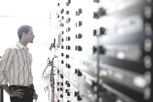 Man looking at cables in server room, side view