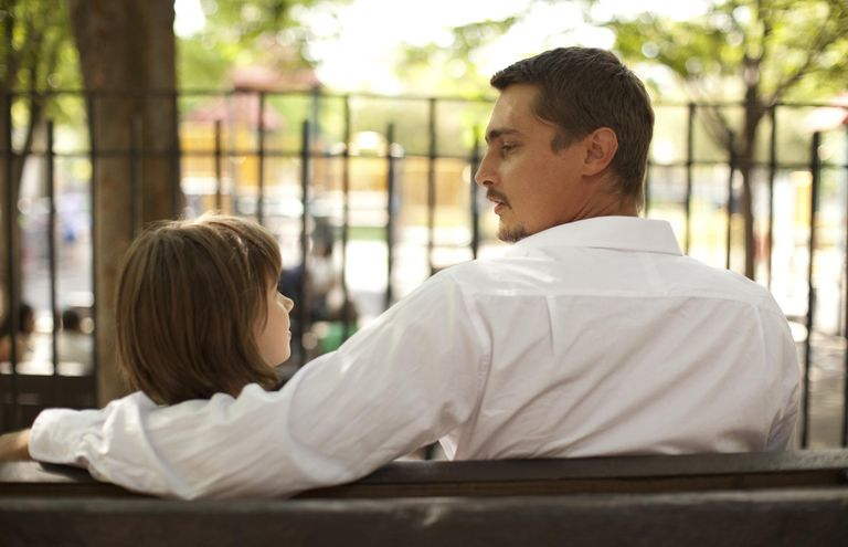 Father talking with daughter on park bench.