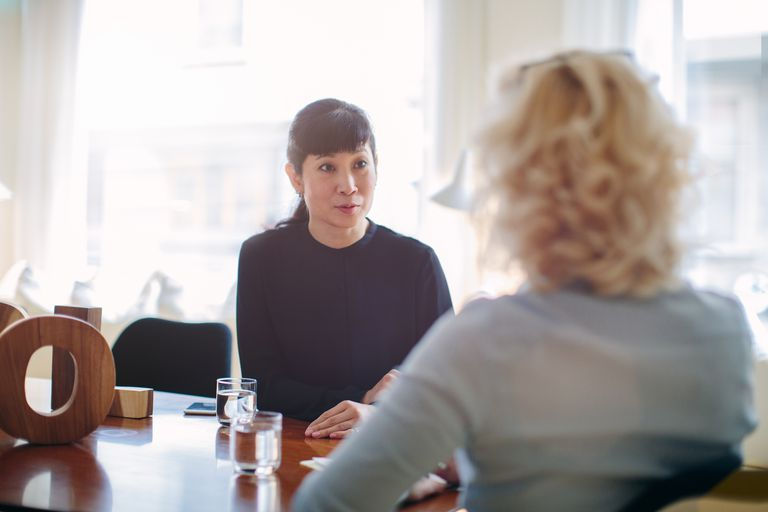 Mature businesswoman interviewing candidate at boardroom table