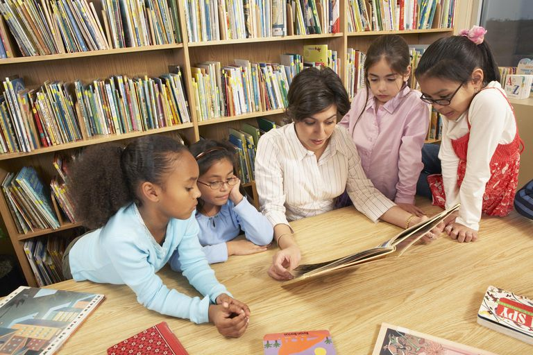 Teacher reading aloud to girls (8-9, 10-11) at table in school library, elevated view
