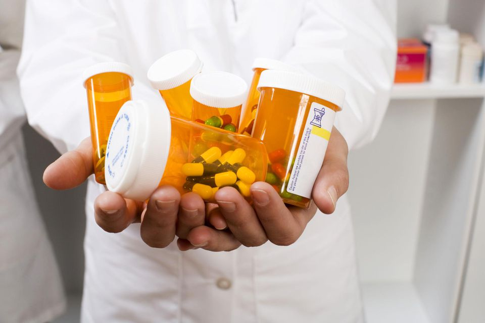 Pharmacist with handful of prescriptions