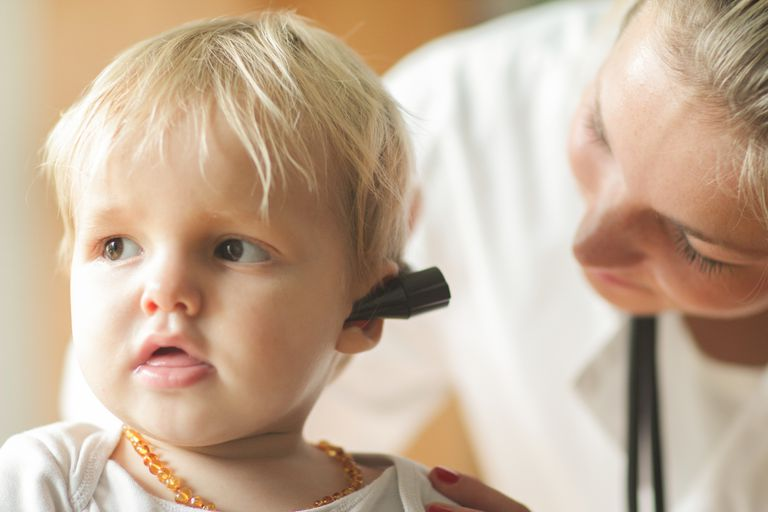 Female doctor looking into baby boy's ear