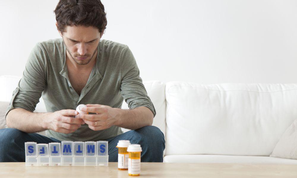 Man putting medication into pill organizer