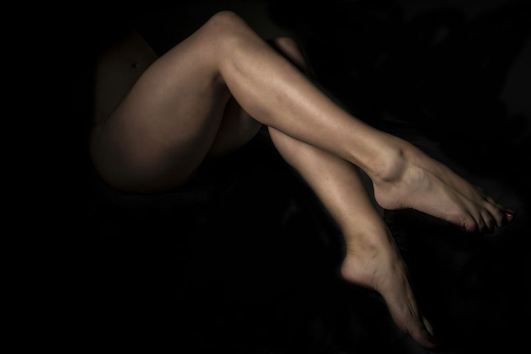 Low Section Of Naked Woman Against Dark Background
