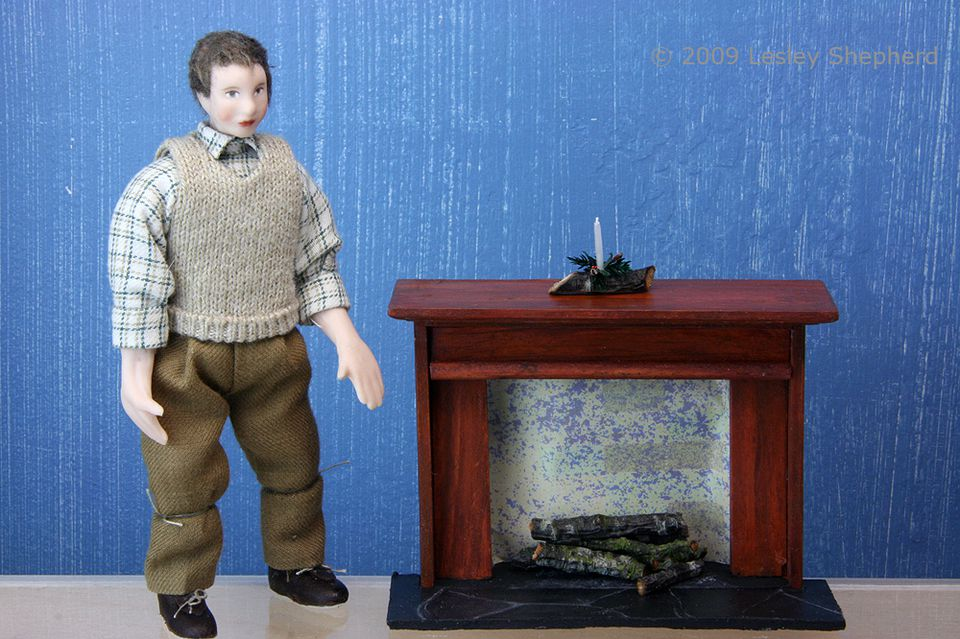 The basic fireplace made from a bashed kitchen hutch is shown beside a doll for scale