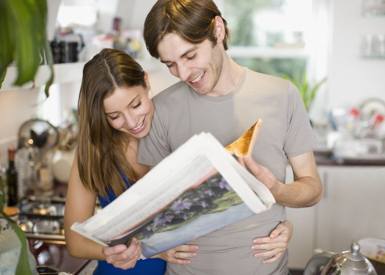 A photo of a young couple looking at a newspaper while eating breakfast