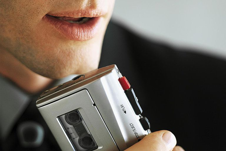 Close-up of a young businessman talking into a Dictaphone