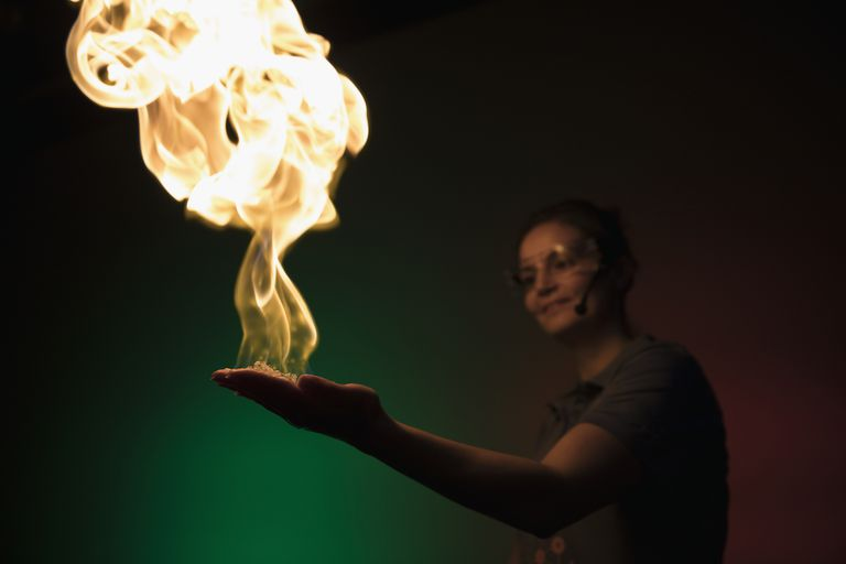 Scientist creating fire demonstration in palm of hand in science center