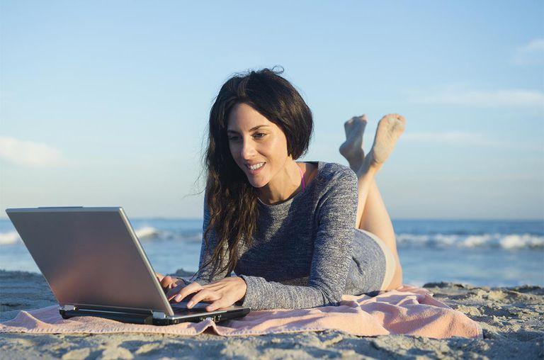Woman using laptop on beach