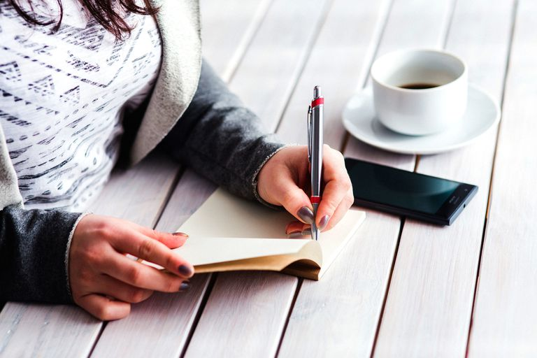 person writing in notebook next to coffee and cell phone