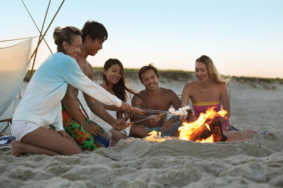 Friends Roasting Marshmallows at a Beach Bonfire